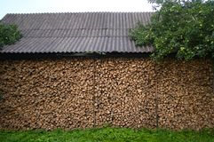 Background of dry chopped firewood logs in a pile. Wall firewood near the house. under roof stock photos