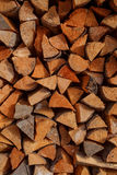 Background of dry chopped firewood logs stacked up on top of each other in a pile. Texture stock photography