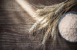 Background Dry wheat ears and flour on old wooden table Stock Photography