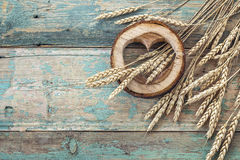 Background with ears of wheat and wooden hearts on old blue boar Royalty Free Stock Photo
