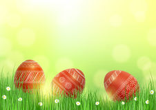 Background with Easter eggs in grass. Bright festive background with three red patterned Easter eggs in the grass Stock Photography