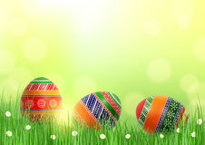 Background with Easter eggs in grass. Bright festive background with three multicolored patterned Easter eggs in grass Royalty Free Stock Photos