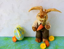 Background for Easter. Easter background with straw bunny, blue egg and yellow and orange flowers royalty free stock image