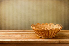 Background with empty basket. On wooden table over grunge wall with strips Royalty Free Stock Photo