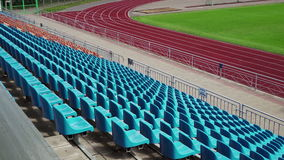 Background of empty blue seats in a stadium, Back view. Running track and football field stock video