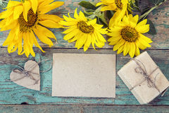 Background with empty card, sunflowers and gift box on old woode Stock Photos