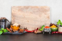 Background with empty cutting board and various oriental spices. Gray wall, copy space Stock Images