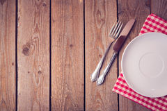 Background with empty plate on wooden table. View from above Royalty Free Stock Image