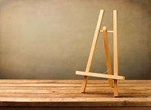 Background with empty wooden easel. On wooden table over grunge background Royalty Free Stock Photos