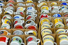 Background of enamel mugs with logos of automobile firms. Royalty Free Stock Images