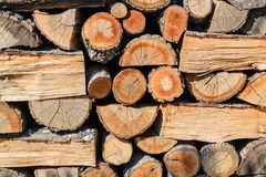 Background of ends of logs and dry firewoods. Close-up  of outdoor stack of wood on a sunny day. Folded and packaged firewood. Woodpile front view royalty free stock images
