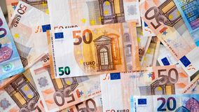 Lots of Euro banknotes of different denominations. Background of Euro cash, with focus on the 50 euros, spread on a surface, concept for poor and wealthy Stock Images