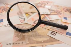 Magnifier focused on euro banknotes. Royalty Free Stock Photography
