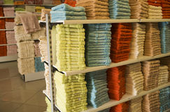 Background exact colorful shopping showcase shelves with many fluffy towels yellow red and blue. Horizontal image selective focus Stock Photo