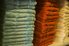Background exact colorful shopping showcase shelves with many fluffy towels yellow red and blue. Horizontal image selective focus Stock Images