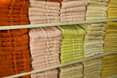 Background exact colorful shopping showcase shelves with many fluffy towels yellow red. Horizontal image selective focus Royalty Free Stock Image