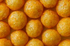 Background of extruded puff cheese balls from above. Yellow Stock Images