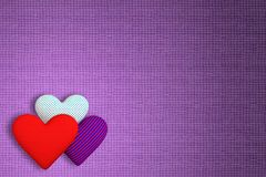 Background of fabric with three volumetric hearts of different p. Rints: red; in a blue-red strip; in the blue peas. The main background is lilac Royalty Free Stock Image