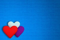 Background of fabric with three volumetric hearts of different p. Rints: red; in a blue-red strip; in the blue peas. The main background is blue Stock Image