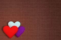 Background of fabric with three volumetric hearts of different p. Rints: red; in a blue-red strip; in the blue peas. The main background is brown Stock Images