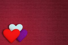 Background of fabric with three volumetric hearts of different p. Rints: red; in a blue-red strip; in the blue peas. The main background is a burgundy color Royalty Free Stock Images
