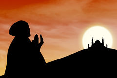 Background of female muslim silhouette  and mosque at sunset Stock Images
