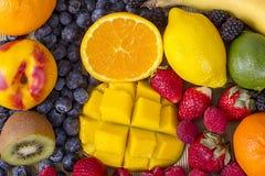 Fresh Fruits And Berries Background. A background filled with fresh fruits and berries - orange, kiwi, banana, lime, tangerine, peach, mango, lemon, strawberries stock photo