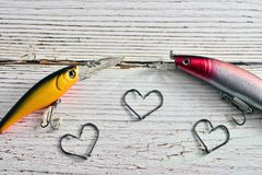 Background with fishing motifs. Concept of passion for the sport of fishing with lures and hooks forming hearts Royalty Free Stock Photography