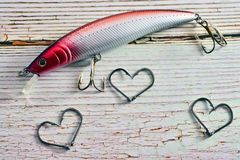 Background with fishing motifs. Concept of passion for the sport of fishing with lures and hooks forming hearts Stock Photo