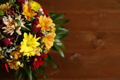 Background with flowers on a wooden board. Background with colourfull autumn flowers bouquet and green leaves on a wooden board Stock Image