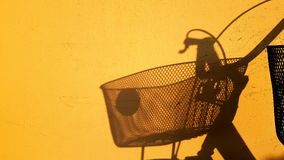 Shadow of A Bicycle On Vivid Yellow Wall. Background Focus on Shadow of A Bicycle On Vivid Yellow Wall Stock Images