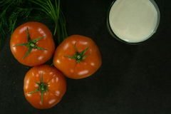 Background food ingredients on black table. Fresh tomatoes and greens, a glass of milk. Stock Photography