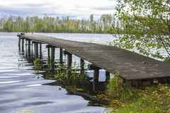Background forest lake surrounded by trees and the wooden footbridge Stock Photo