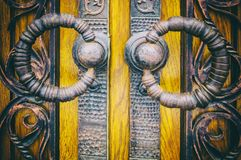 Background with forging elements, metal handles in the form of rings on wooden doors stock photo