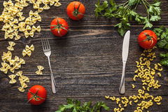 Background with fork and knife pasta, tomatoes and herb on dark Royalty Free Stock Photography