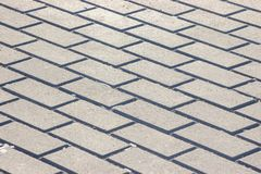 Background in the form of bricks, grey paving slabs. Monotone Gray Brick Stone on The Ground for Street Road royalty free stock photo