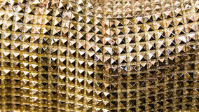 Background formed by a coating of small golden pyramids. Stock Photos