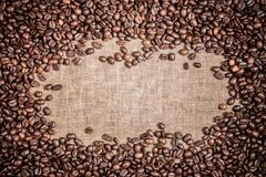 Background with frame of  roasted coffee grains macro close-up on burlap Food backdrop Stock Photo