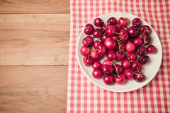 Background with fresh cherries on wooden table with retro filter effect. View from above Royalty Free Stock Photography