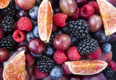 Background of fresh fruits and berries. Ripe blackberries, blueberries, plums, pink grapes, raspberries and figs. Mix berries and. Fruits. Top view. Background stock photo