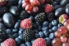 Background of fresh fruits and berries. Ripe blackberries, blueberries, plums and raspberries. Mix berries and fruits. Top view. Background berries and fruits royalty free stock photos