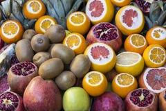 Background of fresh fruits of pomegranate oranges kiwi Stock Photos