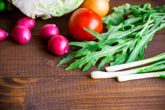 Background with fresh healthy vegetables. Background with old brown boards with fresh healthy vegetables, green onion, radish, cucumber, arugula and cabbage Royalty Free Stock Photo