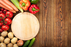 Background of fresh raw vegetables and cutting board. Fresh raw vegetables and cutting board on wooden background, top view Royalty Free Stock Photos