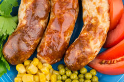 Background with fried sausage, green peas, sweet corn and tomato Royalty Free Stock Photography