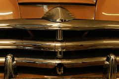 Background - the front part of a retro car. Background - the front part of a vintage car, detail of the radiator lattice from three chromed horizontal bars royalty free stock photography