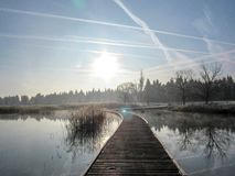 Background with wood path walkway at lake shore on a calm tranquil winter morning. Frost hoar wooden pier royalty free stock image