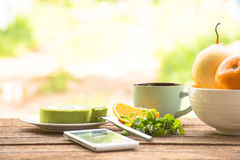 Background fruit in bowl and coffee cup with green tea cake and mint with smartphone.On wooden background outdoor view and holiday. Background fruit in bowl and Stock Photos