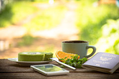 Background fruit  and coffee cup with green tea cake and mint with smartphone and passport.All screen about travel. Background fruit in bowl and juice with Royalty Free Stock Images