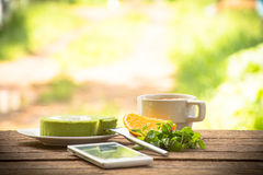 Background fruit  and green tea cake and mint with smartphone.On wooden background outdoor view and holiday with rela. Background fruit  with green tea cake and Royalty Free Stock Photography